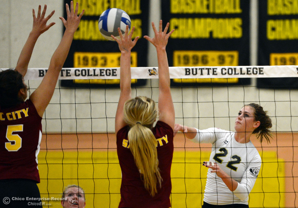 Description of . Butte College's #22 Courtney Robinson (right) spikes against Sac City College's #8 Kylee Hardy (center) and #15 Raven Balafoutis (left) in the first game of their women's volleyball match at Butte's Cowan Gym Wednesday, September 25, 2013, in Oroville, Calif.  (Jason Halley/Chico Enterprise-Record)