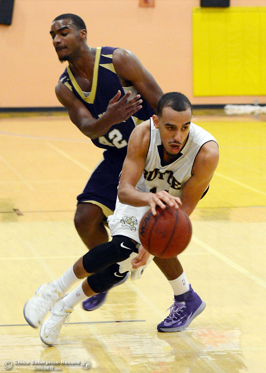 Description of . Butte College\'s #11 Jamaal Davis (right) dribbles against San Jose City College\'s #42 Andre Russell (left ) in the second half of their men\'s basketball game at Butte\'s Cowan Gym Friday, February 28, 2014 in Oroville, Calif.  (Jason Halley-Chico Enterprise-Record)