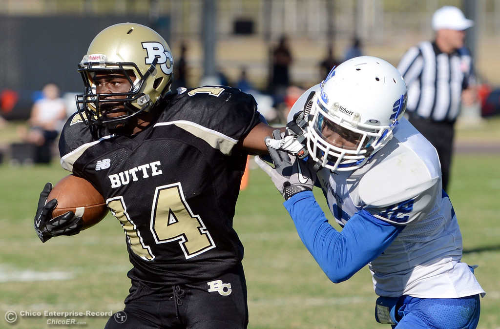 . Butte College\'s #14 Robert Frazier (left) is tackled against College of San Mateo\'s #12 Taylor Mashack (right) in the third quarter of their football game at Butte\'s Cowan Stadium Saturday, November 2, 2013 in Oroville, Calif.  (Jason Halley/Chico Enterprise-Record)