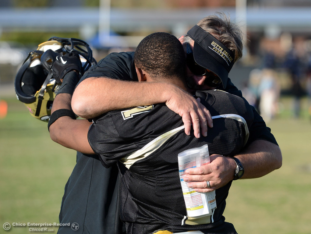 . Butte College head coach Jeff Jordan (back) embraces #1 Wes McCoy (front) after they won against San Mateo College in the fourth quarter of their football game at Butte\'s Cowan Stadium Saturday, November 2, 2013 in Oroville, Calif.  (Jason Halley/Chico Enterprise-Record)