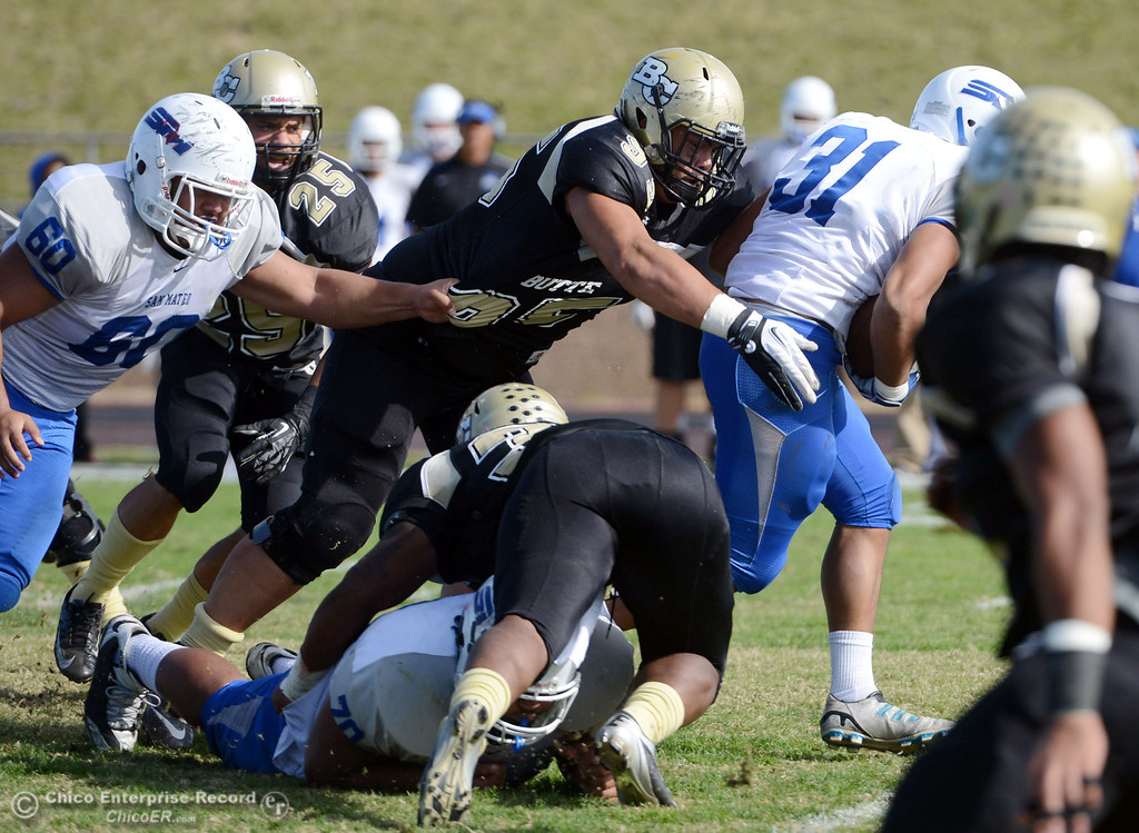 . Butte College\'s #95 Mark Rosenquist (left) tackles against San Mateo College\'s #31 Michael Latu (right) in the first quarter of their football game at Butte\'s Cowan Stadium Saturday, November 2, 2013 in Oroville, Calif.  (Jason Halley/Chico Enterprise-Record)
