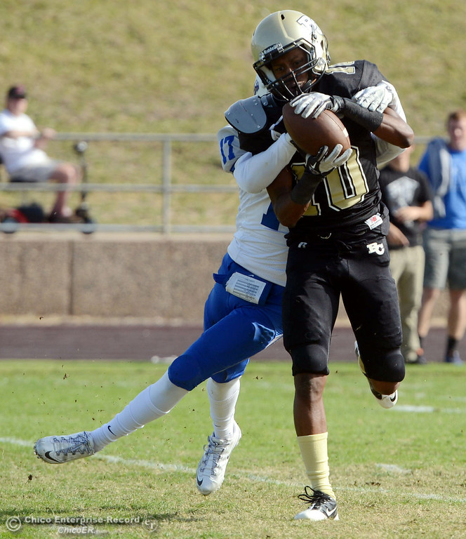 . Butte College\'s #10 CJ Grice (right) completes a pass against San Mateo College\'s #17 Deshane Hines (left) in the first quarter of their football game at Butte\'s Cowan Stadium Saturday, November 2, 2013 in Oroville, Calif.  (Jason Halley/Chico Enterprise-Record)