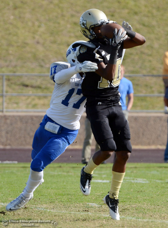 . Butte College\'s #10 CJ Grice (right) completes a catch against San Mateo College\'s #17 Deshane Hines (left) in the first quarter of their football game at Butte\'s Cowan Stadium Saturday, November 2, 2013 in Oroville, Calif.  (Jason Halley/Chico Enterprise-Record)