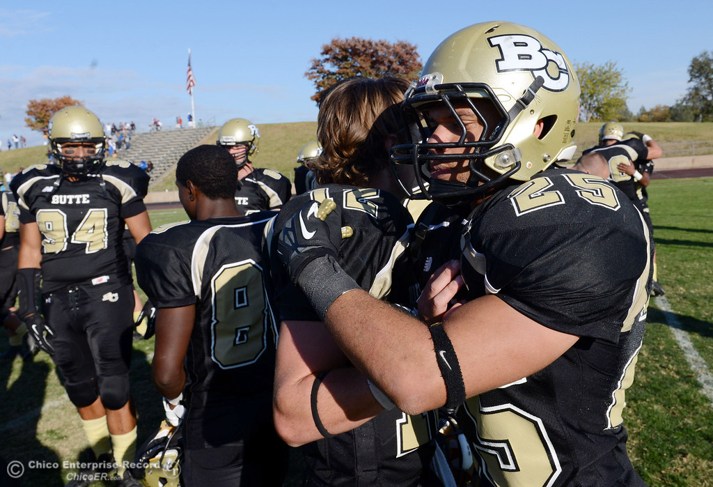 . Butte College\'s #12 Thomas Staurt (left) and #25 Gooden De\'Aundray (right) celebrate their win against College of San Mateo at the end of the fourth quarter of their football game at Butte\'s Cowan Stadium Saturday, November 2, 2013 in Oroville, Calif.  (Jason Halley/Chico Enterprise-Record)