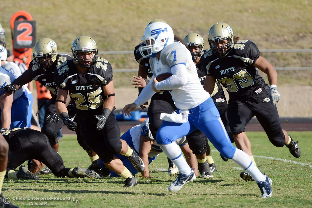 . Butte College\'s #25 Gooden De\'Aundray (left) and #99 Leopeni Siania (right) defend against College of San Mateo\'s #7 Casey Wichman (center) who runs for a touchdown in the third quarter of their football game at Butte\'s Cowan Stadium Saturday, November 2, 2013 in Oroville, Calif.  (Jason Halley/Chico Enterprise-Record)