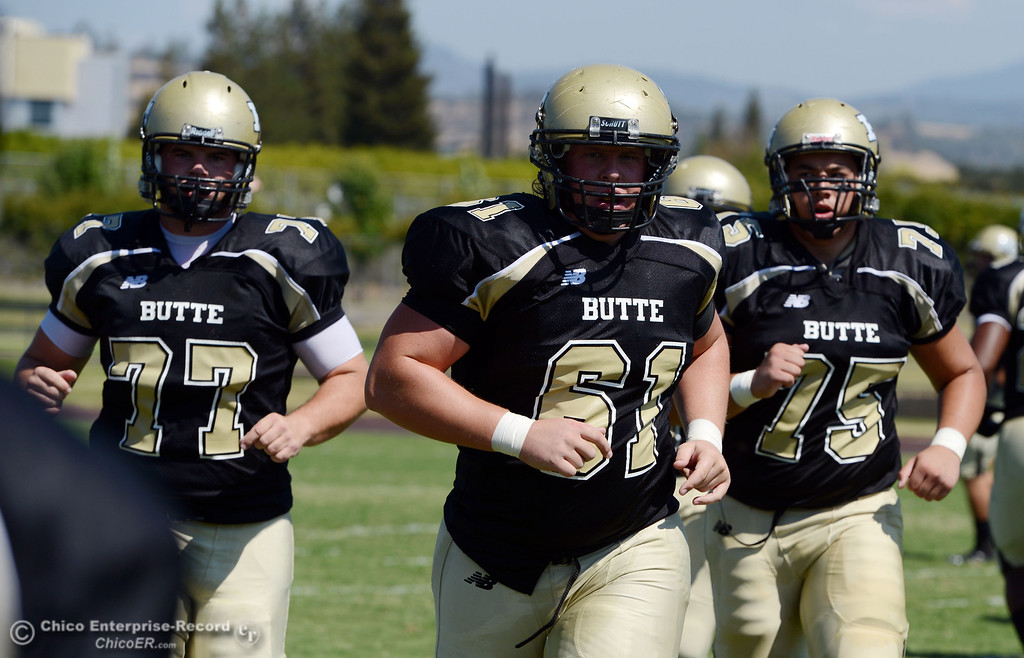 Description of . Butte College's #77 Scott Batchelder, #61 Jacob Bigham and #75 Jacob Vazquez (left to right) come off the field against College of the Siskiyous in the first quarter of their football game at Butte's Cowan Stadium on Saturday, September 14, 2013, in Oroville, Calif. (Jason Halley/Chico Enterprise-Record)