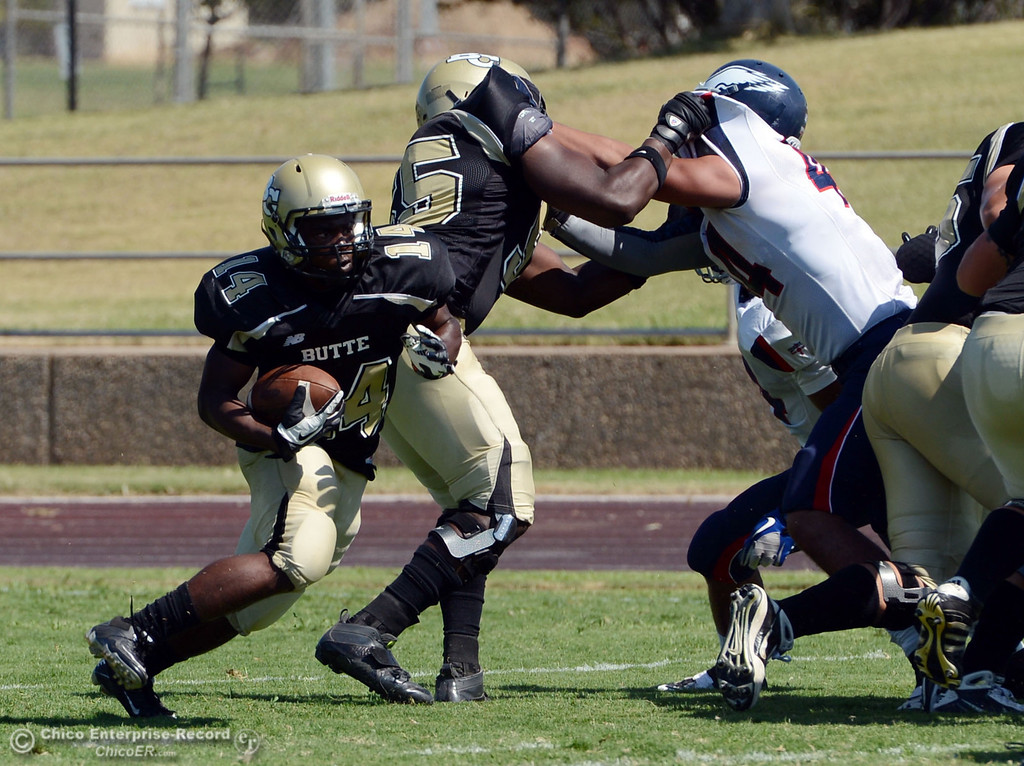 Description of . Butte College's #14 Robert Frazier (left) rushes against College of the Siskiyous in the first quarter of their football game at Butte's Cowan Stadium on Saturday, September 14, 2013, in Oroville, Calif. (Jason Halley/Chico Enterprise-Record)