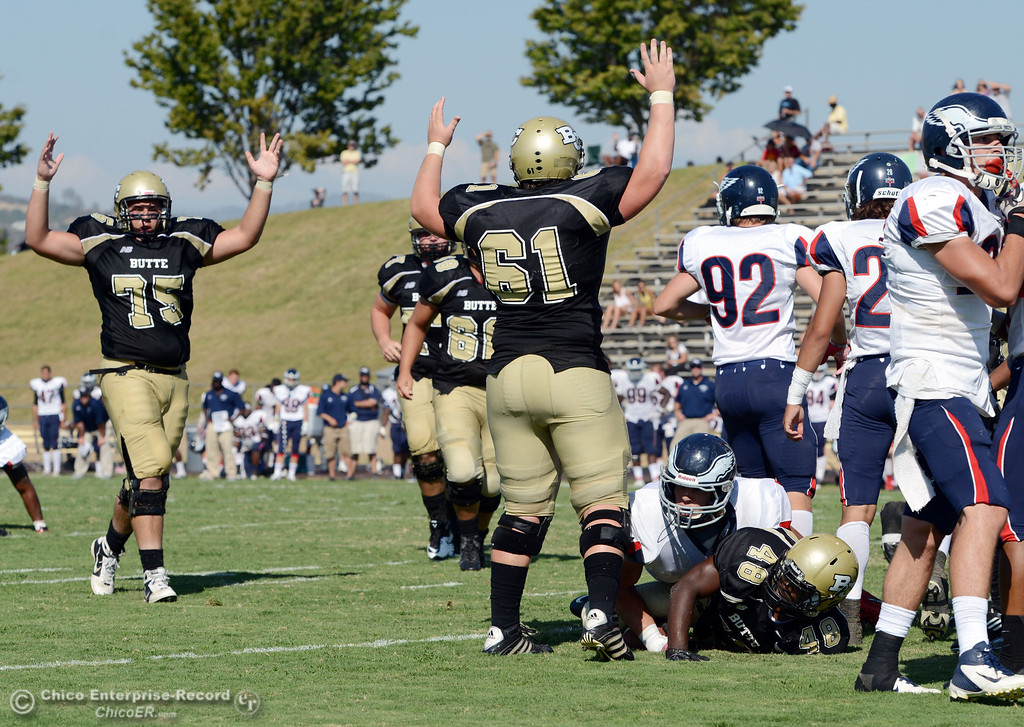 Description of . Butte College's #75 Christopher Siliga (left) and #61 Jacob Bigham (center) react to #48 Michael Faggett (bottom) scoring a touchdown against College of the Siskiyous in the fourth quarter of their football game at Butte's Cowan Stadium on Saturday, September 14, 2013, in Oroville, Calif. (Jason Halley/Chico Enterprise-Record)