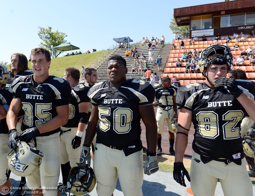 Description of . Butte College's #85 Richard Murphy, #50 Joshua Wormley, and #82 Greg Cannon (left to right) against College of the Siskiyous before the first quarter of their football game at Butte's Cowan Stadium on Saturday, September 14, 2013, in Oroville, Calif. (Jason Halley/Chico Enterprise-Record)