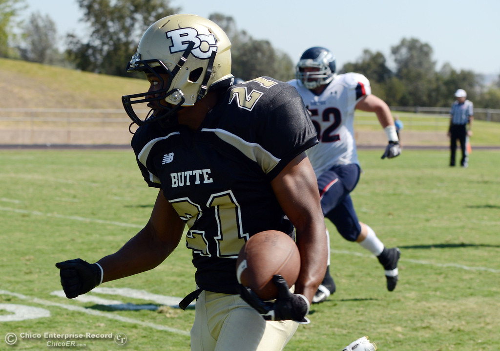 Description of . Butte College's #21 Marvel Harris rushes against College of the Siskiyous in the second quarter of their football game at Butte's Cowan Stadium on Saturday, September 14, 2013, in Oroville, Calif. (Jason Halley/Chico Enterprise-Record)
