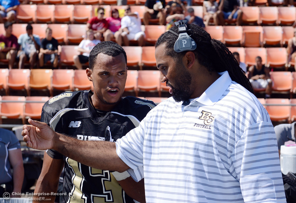 Description of . Butte College's coach Bobby Bernal (right) talks to #13 Cedric Anderson (left) against College of the Siskiyous before the first quarter of their football game at Butte's Cowan Stadium on Saturday, September 14, 2013, in Oroville, Calif. (Jason Halley/Chico Enterprise-Record)