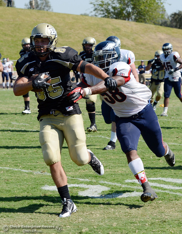 Description of . Butte College's #85 Richard Murphy (left) rushes against College of the Siskiyous' #58 Tyrese Lyons (right) in the third quarter of their football game at Butte's Cowan Stadium on Saturday, September 14, 2013, in Oroville, Calif. (Jason Halley/Chico Enterprise-Record)