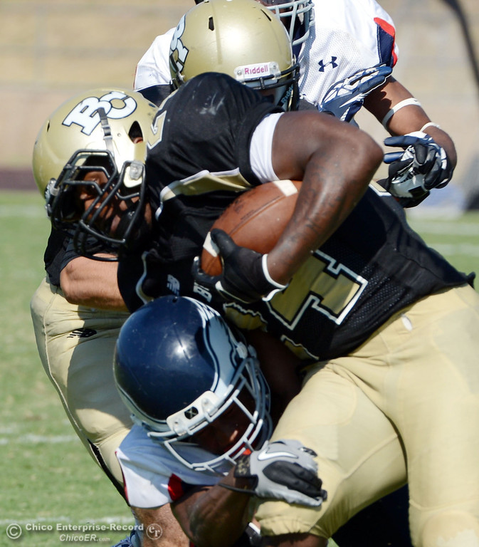 Description of . Butte College's #24 Kendall WIlliams (center) is tackled against College of the Siskiyous in the third quarter of their football game at Butte's Cowan Stadium on Saturday, September 14, 2013, in Oroville, Calif. (Jason Halley/Chico Enterprise-Record)