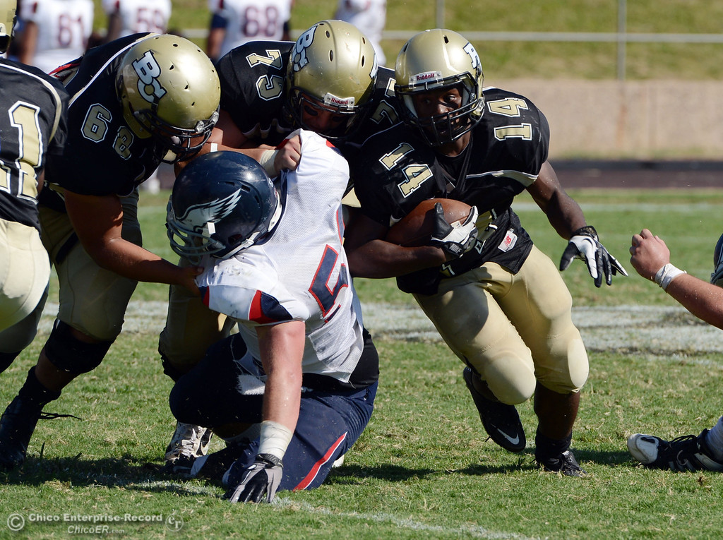 Description of . Butte College's #14Robert Frazier (center) rushes against College of the Siskiyous in the third quarter of their football game at Butte's Cowan Stadium on Saturday, September 14, 2013, in Oroville, Calif. (Jason Halley/Chico Enterprise-Record)