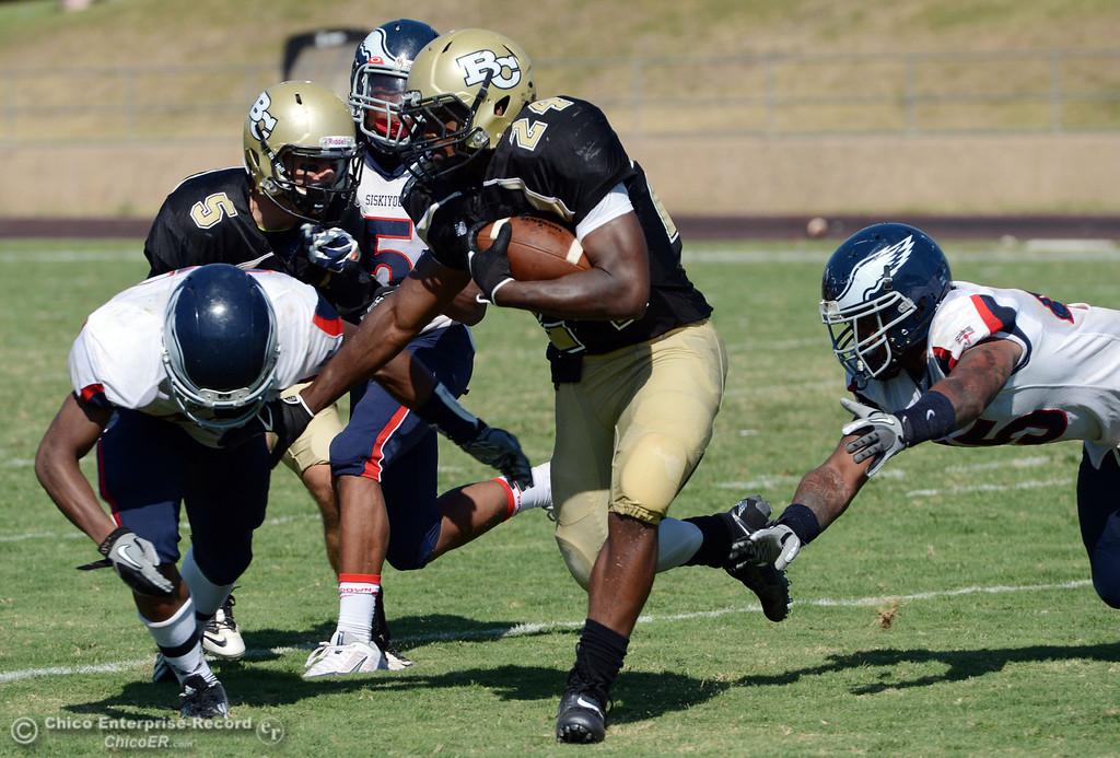 Description of . Butte College's #24 Kendall WIlliams (center) rushes against College of the Siskiyous in the third quarter of their football game at Butte's Cowan Stadium on Saturday, September 14, 2013, in Oroville, Calif. (Jason Halley/Chico Enterprise-Record)