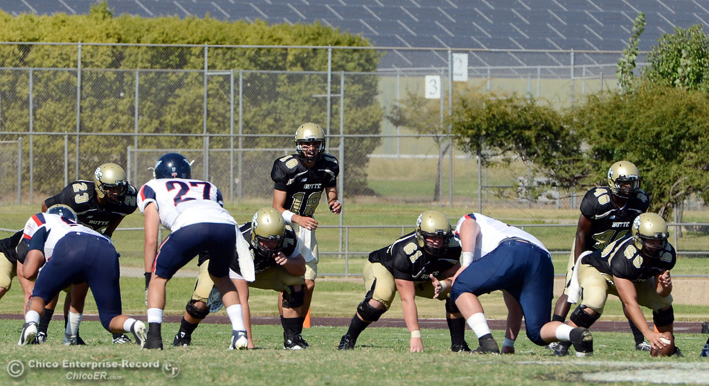 Description of . Butte College's #18 Eric Ascensio (center) readies the snap against College of the Siskiyous in the fourth quarter of their football game at Butte's Cowan Stadium on Saturday, September 14, 2013, in Oroville, Calif. (Jason Halley/Chico Enterprise-Record)