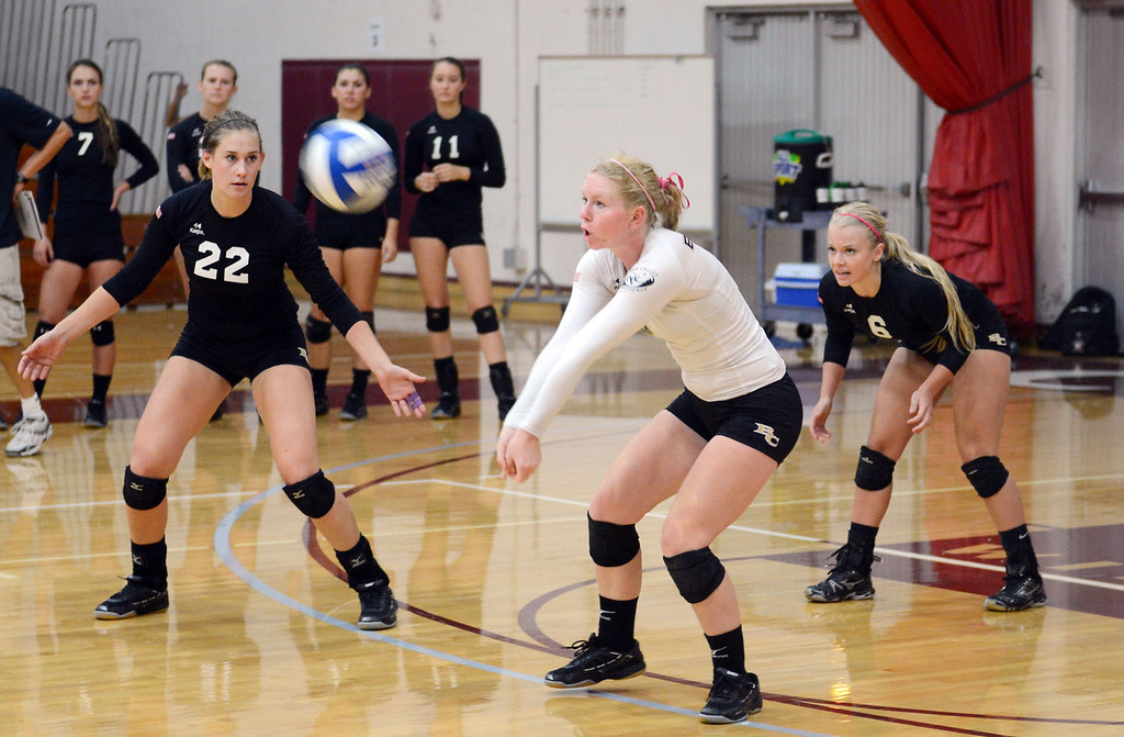 Description of . Butte College's #8 Mikaela Woodbury (center) takes a dig as #22 Courtney Robinson (left) and #6 Lacie Landrum (right) look on against Chico State in their volleyball game at CSUC Acker Gym Saturday, August 24, 2013 in Chico, Calif.  (Jason Halley/Chico Enterprise-Record)
