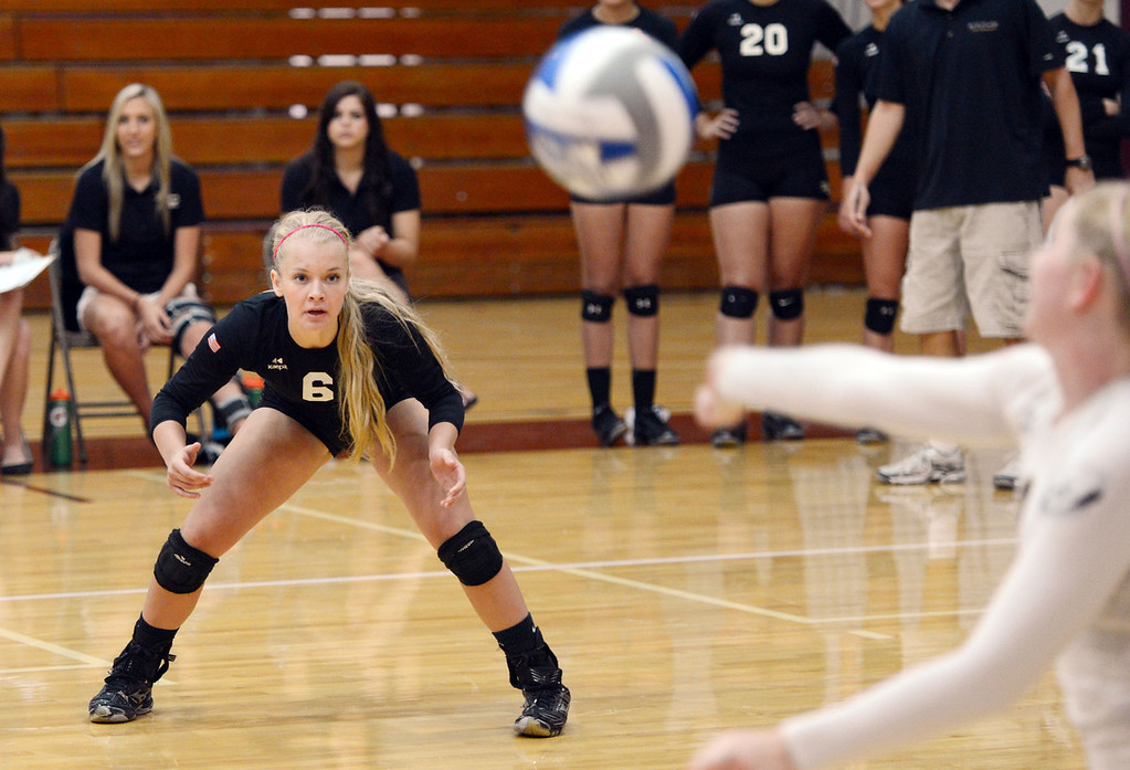 Description of . Butte College's #6 Lacie Landrum (left) watches #8 Mikaela Woodbury (right) hit the ball against Chico State in their volleyball game at CSUC Acker Gym Saturday, August 24, 2013 in Chico, Calif.  (Jason Halley/Chico Enterprise-Record)