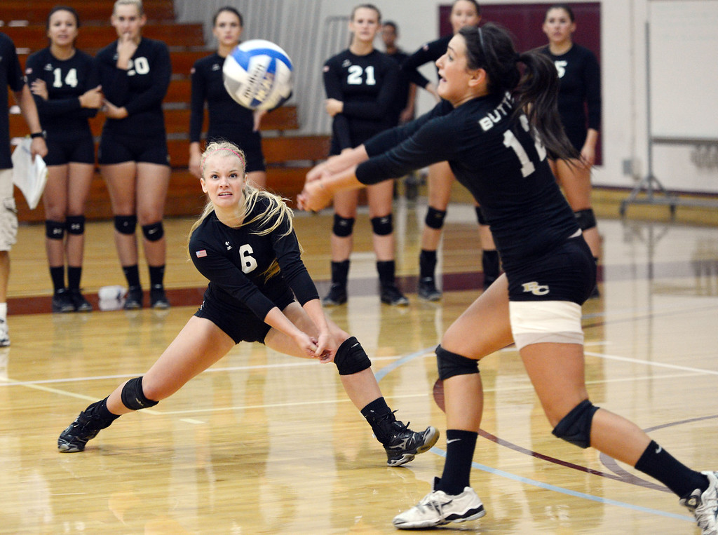Description of . Butte College's #6 Lacie Landrum (left) watches #12 Callie Flood (right) hit against Chico State in their volleyball game at CSUC Acker Gym Saturday, August 24, 2013 in Chico, Calif.  (Jason Halley/Chico Enterprise-Record)