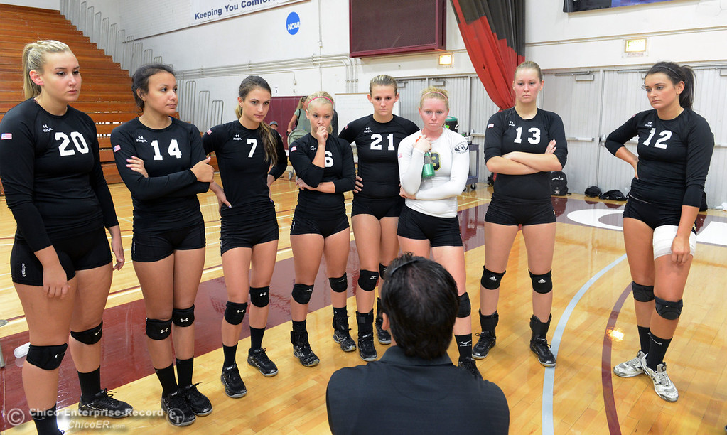 Description of . Butte College #20 Erika Click, #14 Gabby Delarosa, #7 Taylor Johnson, #6 Lacie Landrum, #21 Drew Tattam, #8 Mikaela Woodbury, #13 Emilie Aase, and #12 Callie Flood (left to right) listen to coach Dave Davis (center) talk to the team as they play against Chico State in their volleyball game at CSUC Acker Gym Saturday, August 24, 2013 in Chico, Calif.  (Jason Halley/Chico Enterprise-Record)