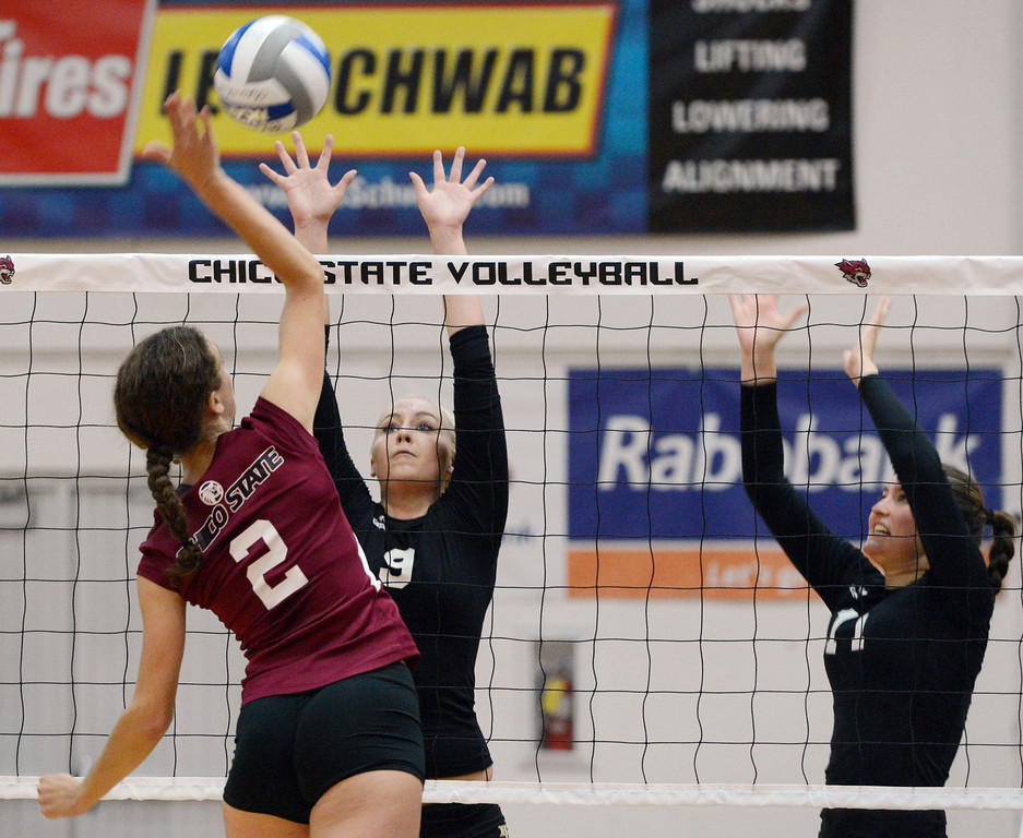 Description of . Butte College's #9 Colleen Tade (right) attempts to block against Chico State's #2 Ellie Larronde (left) in their volleyball game at CSUC Acker Gym Saturday, August 24, 2013 in Chico, Calif.  (Jason Halley/Chico Enterprise-Record)