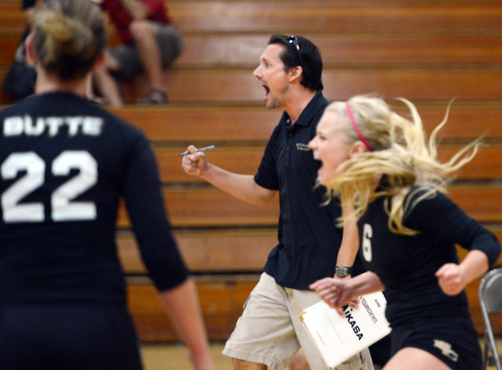 Description of . Butte College's #22 Courtney Robinson, coach Dave Davis and #6 Lacie Landrum (left to right) react to a score against Chico State in their volleyball game at CSUC Acker Gym Saturday, August 24, 2013 in Chico, Calif.  (Jason Halley/Chico Enterprise-Record)
