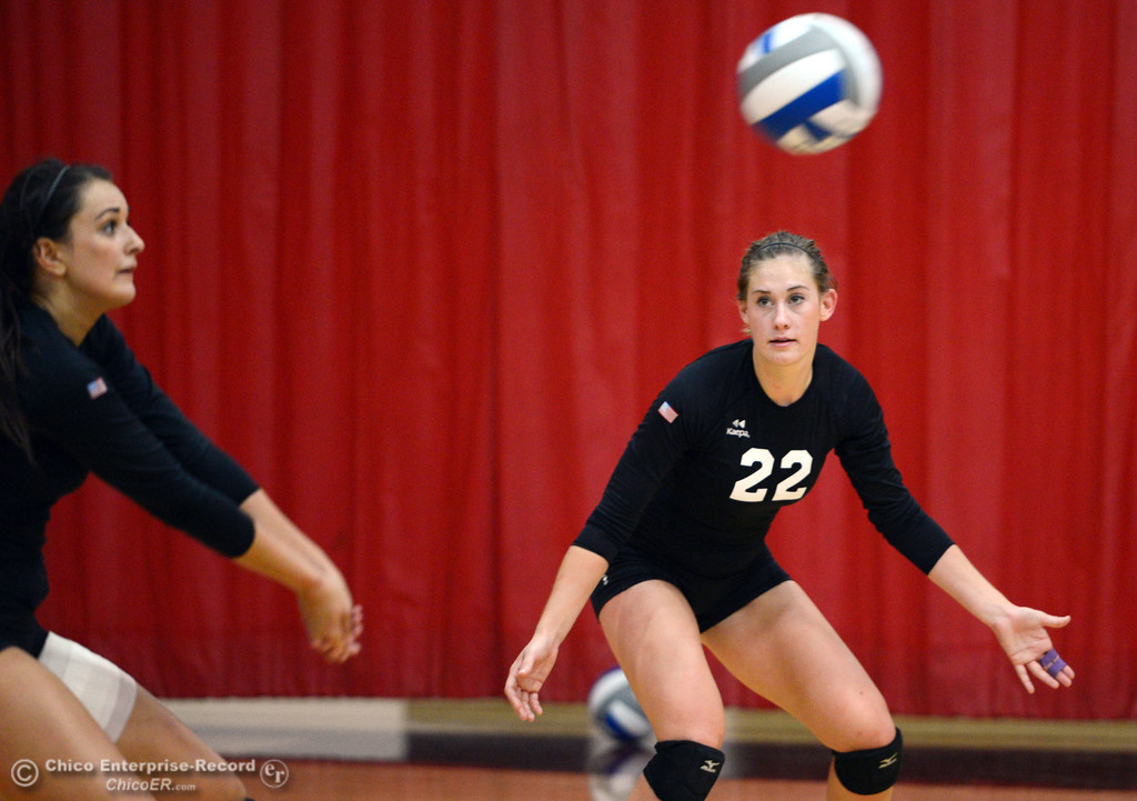 Description of . Butte College's #22 Courtney Robinson (right) watches #12 Callie Flood (left) bump against Chico State in their volleyball game at CSUC Acker Gym Saturday, August 24, 2013 in Chico, Calif.  (Jason Halley/Chico Enterprise-Record)