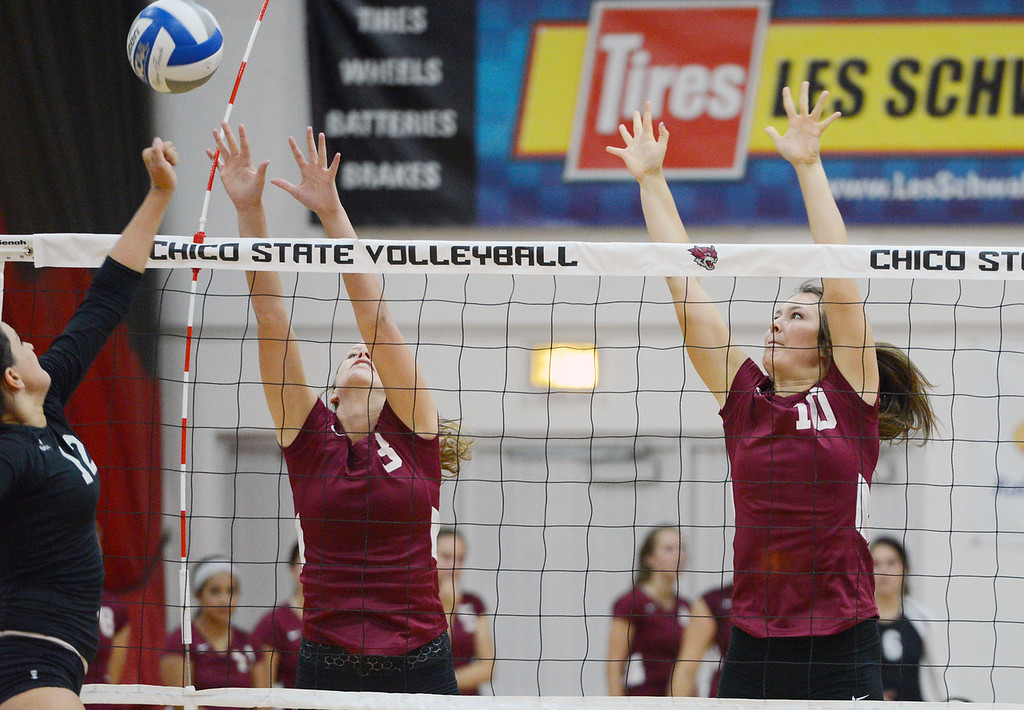 Description of . Butte College's #12 Callie Flood (left) spikes against Chico State's #3 Haley Uhland (center) and #10 Ashton Kershner (right) in their volleyball game at CSUC Acker Gym Saturday, August 24, 2013 in Chico, Calif.  (Jason Halley/Chico Enterprise-Record)