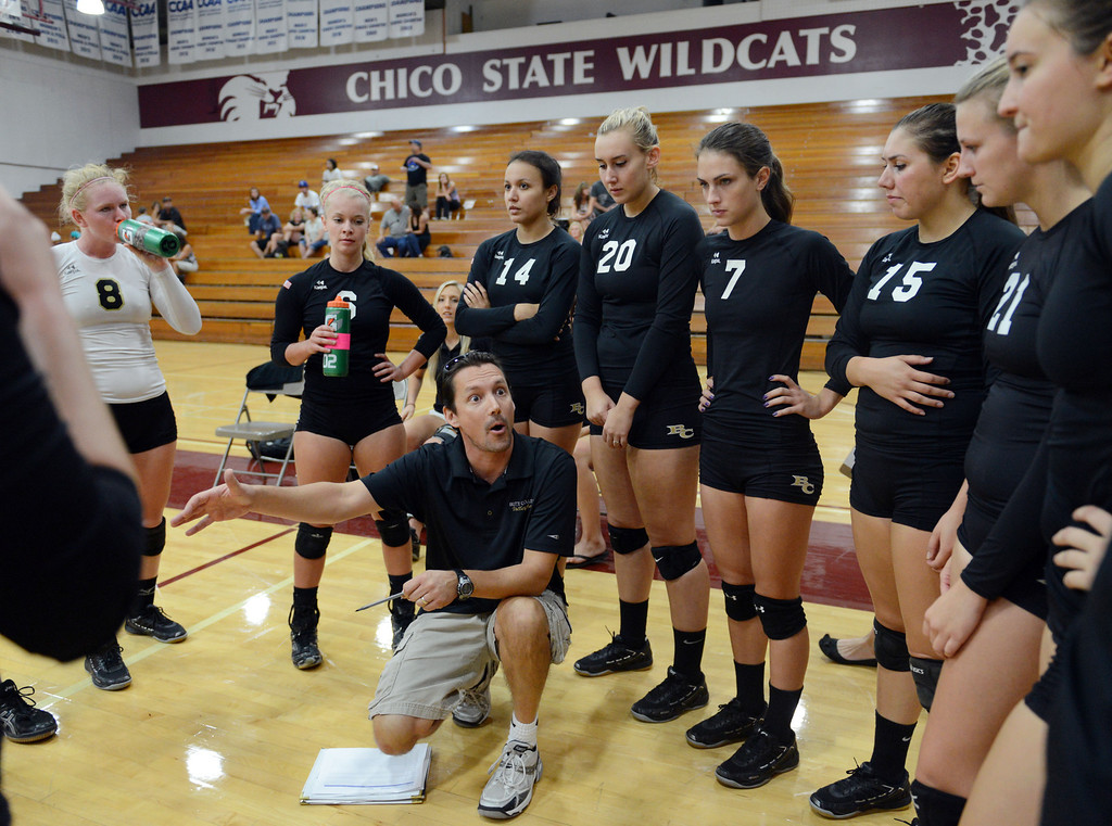 Description of . Butte College coach Dave Davis (center) talks to #8 Mikaela Woodbury, #6 Lacie Landrum, #14 Gabby Delarosa, #20 Erika Click, #7 Taylor Johnson, #15 Kristen Keys, #21 Drew Tattam and others (left to right) against Chico State in their volleyball game at CSUC Acker Gym Saturday, August 24, 2013 in Chico, Calif.  (Jason Halley/Chico Enterprise-Record)