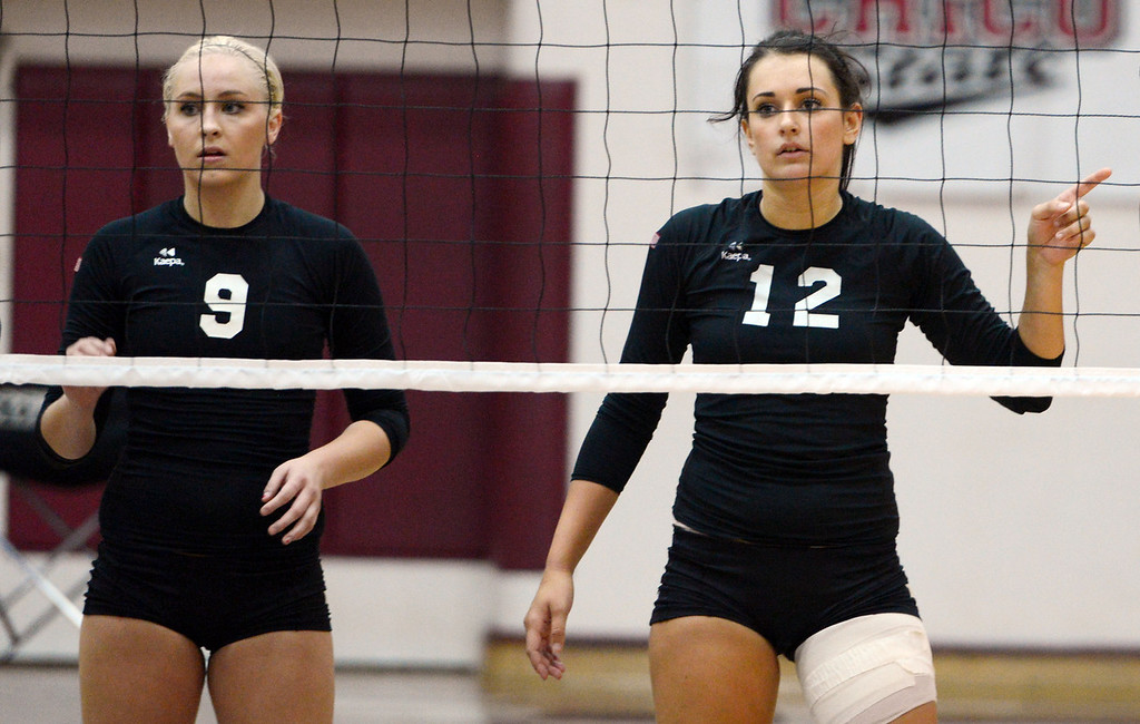 Description of . Butte College's #9 Coleen Tade (left) and #12 Callie Flood (right) ready against Chico State in their volleyball game at CSUC Acker Gym Saturday, August 24, 2013 in Chico, Calif.  (Jason Halley/Chico Enterprise-Record)