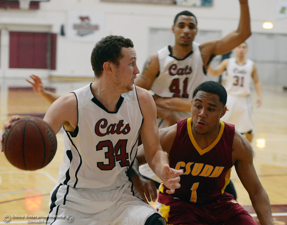 Description of . Chico State\'s #34 Drew Kitchens (left) dribbles against Cal State Dominguez Hills\' #1 Chris Carvin (right) in the first half of their men\'s basketball game at CSUC Acker Gym Friday, January 10, 2014 in Chico, Calif.  (Jason Halley/Chico Enterprise-Record)