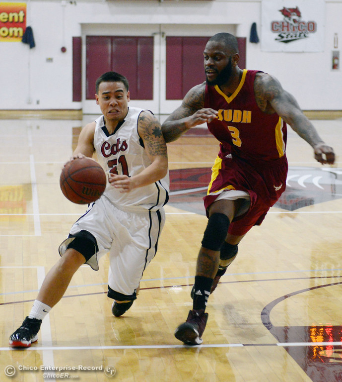 Description of . Chico State\'s #31 Mike Rosaroso (left) dribbles against Cal State Dominguez Hills\' #3 DeShaun Freeman (right) in the first half of their men\'s basketball game at CSUC Acker Gym Friday, January 10, 2014 in Chico, Calif.  (Jason Halley/Chico Enterprise-Record)