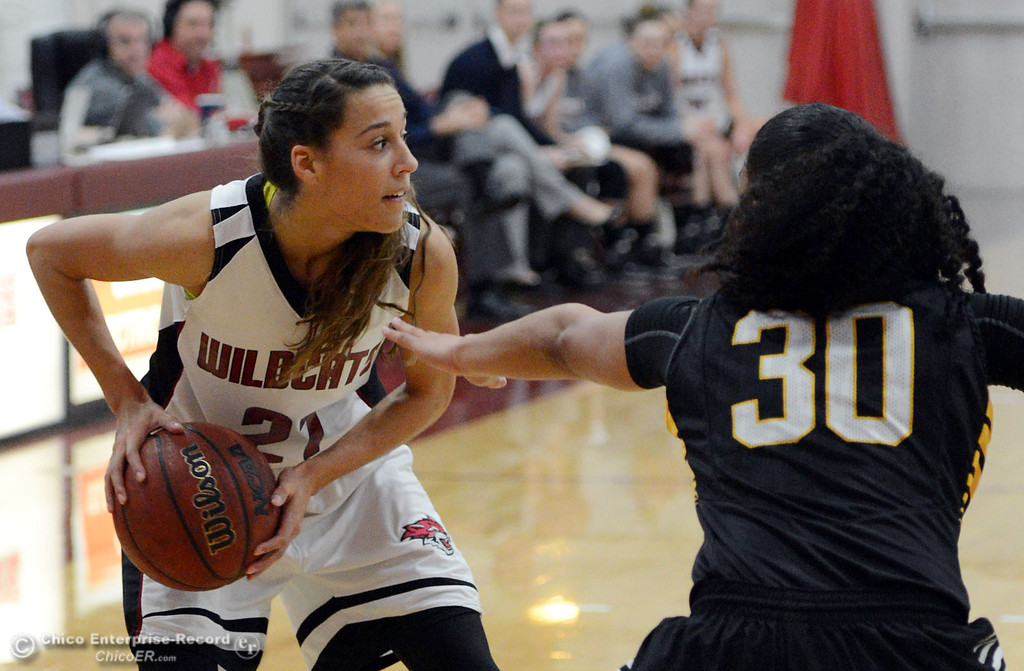 Description of . Chico State\'s #21 Courtney Hamilton (left) looks to pass against Cal State L.A.\'s #30 Kaija Powell (right) in the first half of their women\'s basketball game at CSUC Acker Gym Saturday, January 11, 2014 in Chico, Calif.  (Jason Halley/Chico Enterprise-Record)