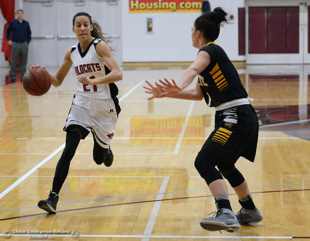 Description of . Chico State\'s #21 Courtney Hamilton (left) dribbles against Cal State L.A.\'s #1 Paige Melville (right) in the first half of their women\'s basketball game at CSUC Acker Gym Saturday, January 11, 2014 in Chico, Calif.  (Jason Halley/Chico Enterprise-Record)