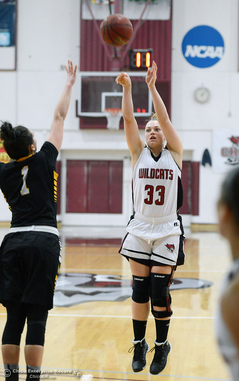 Description of . Chico State\'s #33 Ashtyn Anderson (right) takes a shot against Cal State L.A.\'s #1 Paige Melville (left) in the first half of their women\'s basketball game at CSUC Acker Gym Saturday, January 11, 2014 in Chico, Calif.  (Jason Halley/Chico Enterprise-Record)