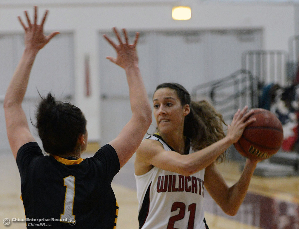 Description of . Chico State\'s #21 Courtney Hamilton (right) looks to pass against Cal State L.A.\'s #1 Paige Melville (left) in the first half of their women\'s basketball game at CSUC Acker Gym Saturday, January 11, 2014 in Chico, Calif.  (Jason Halley/Chico Enterprise-Record)
