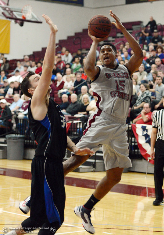 . Chico State\'s #15 Amir Carraway (right) takes a shot against Cal State San Bernardino\'s #32 Taylor Statham (left) in the first half of their men\'s basketball game at CSUC Acker Gym Saturday, February 8, 2014 in Chico, Calif.  (Jason Halley/Chico Enterprise-Record)