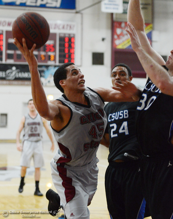 . Chico State\'s #45 Jordan Semple (left) goes up for a shot against Cal State San Bernardino\'s #24 Jordan Burris (center) and #30 Casey Oldemoppen (right) in the first half of their men\'s basketball game at CSUC Acker Gym Saturday, February 8, 2014 in Chico, Calif.  (Jason Halley/Chico Enterprise-Record)