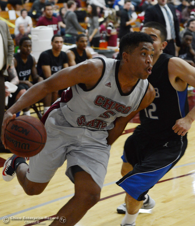 . Chico State\'s #15 Amir Carraway (left) dribbles against Cal State San Bernardino\'s #12 Juan Martinez (right) in the first half of their men\'s basketball game at CSUC Acker Gym Saturday, February 8, 2014 in Chico, Calif.  (Jason Halley/Chico Enterprise-Record)