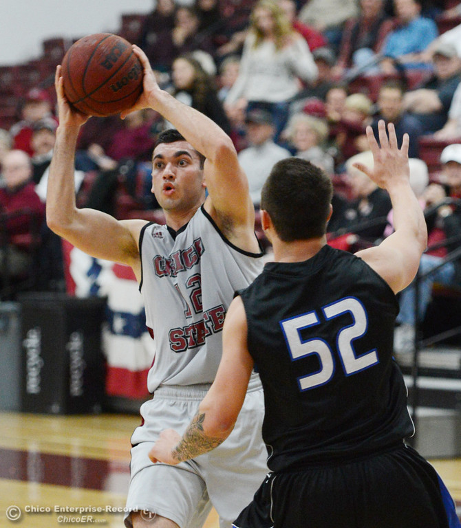 . Chico State\'s #12 Giordano Estrada (left) looks to pass against Cal State San Bernardino\'s #52 Zeke DeBlase (right) in the first half of their men\'s basketball game at CSUC Acker Gym Saturday, February 8, 2014 in Chico, Calif.  (Jason Halley/Chico Enterprise-Record)