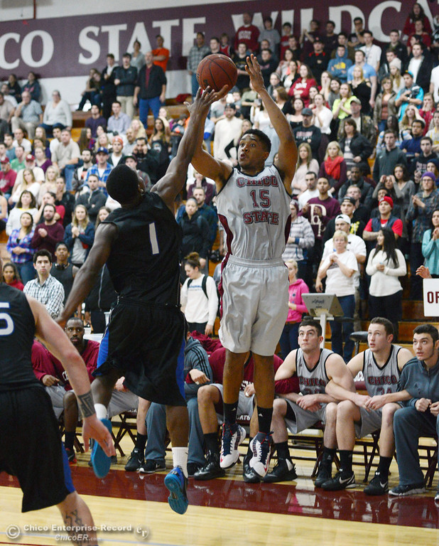 . Chico State\'s #15 Amir Carraway (right) takes a shot against Cal State San Bernardino\'s #1 Kirby Gardner (left) in the second half of their men\'s basketball game at CSUC Acker Gym Saturday, February 8, 2014 in Chico, Calif.  (Jason Halley/Chico Enterprise-Record)