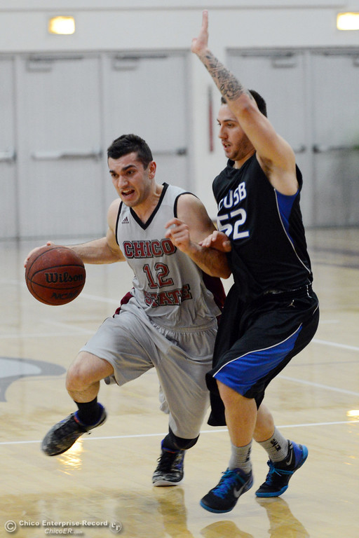 . Chico State\'s #12 Giordano Estrada (left) dribbles against Cal State San Bernardino\'s #52 Zeke DeBlase (right) in the first half of their men\'s basketball game at CSUC Acker Gym Saturday, February 8, 2014 in Chico, Calif.  (Jason Halley/Chico Enterprise-Record)