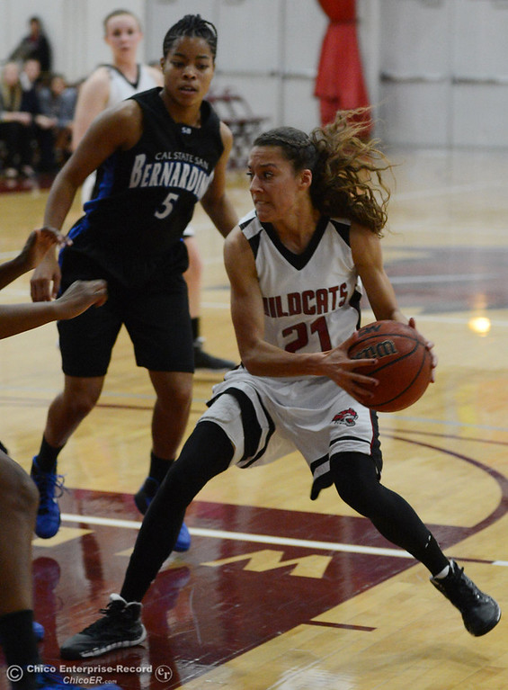 . Chico State\'s #21 Courtney Hamilton (right) dribbles against Cal State San Bernardino\'s #5 Tayllor Gipson (left) in the first half of their women\'s basketball game at CSUC Acker Gym Saturday, February 8, 2014 in Chico, Calif.  (Jason Halley/Chico Enterprise-Record)