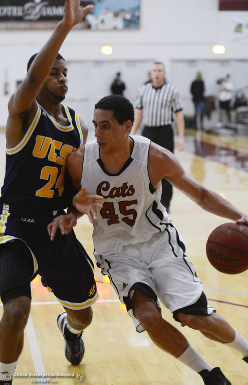 Description of . Chico State's #45 Jordan Semple (right) dribbles against UC San Diego's #24 Treavon Francis (left) in the first half of their men's basketball game at CSUC Acker Gym Friday, February 7, 2014 in Chico, Calif.  (Jason Halley/Chico Enterprise-Record)