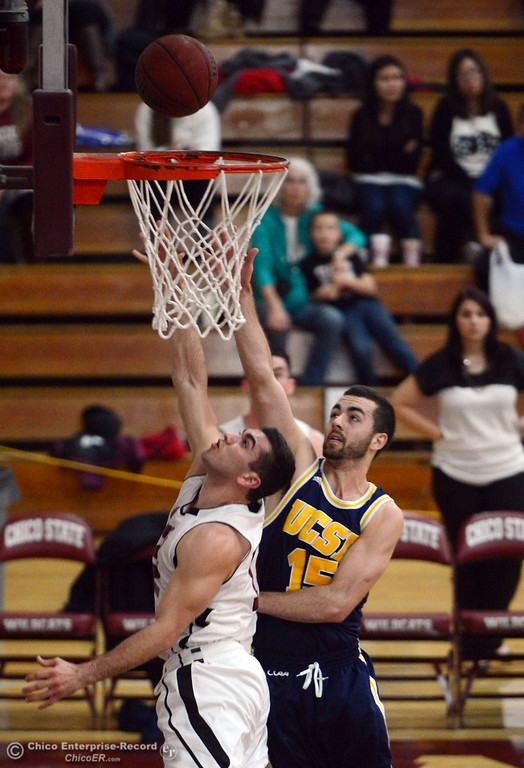Description of . Chico State's #12 Giordano Estrada (left) goes up for a shot against UC San Diego's #15 Aleks Lipovic (right) in the first half of their men's basketball game at CSUC Acker Gym Friday, February 7, 2014 in Chico, Calif.  (Jason Halley/Chico Enterprise-Record)