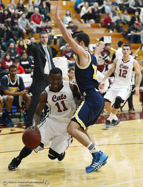 Description of . Chico State's #11 Rashad Parker (left) dribbles against UC San Diego's #15 Aleks Lipovic (right) in the first half of their men's basketball game at CSUC Acker Gym Friday, February 7, 2014 in Chico, Calif.  (Jason Halley/Chico Enterprise-Record)