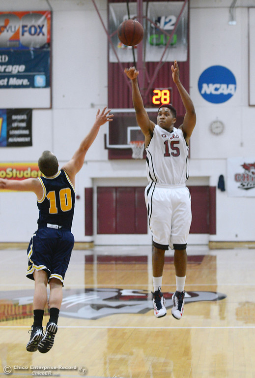 Description of . Chico State's #15 Amir Carraway (right) takes a shot against UC San Diego's #10 James McCann (left) in the first half of their men's basketball game at CSUC Acker Gym Friday, February 7, 2014 in Chico, Calif.  (Jason Halley/Chico Enterprise-Record)