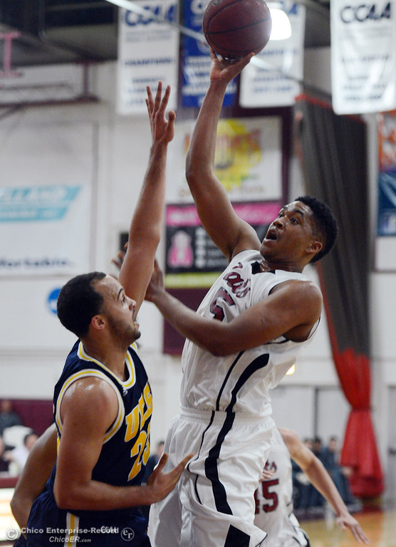 Description of . Chico State's #15 Amir Carraway (right) goes up for a shot against UC San Diego's #23 Hunter Walker (left) in the first half of their men's basketball game at CSUC Acker Gym Friday, February 7, 2014 in Chico, Calif.  (Jason Halley/Chico Enterprise-Record)
