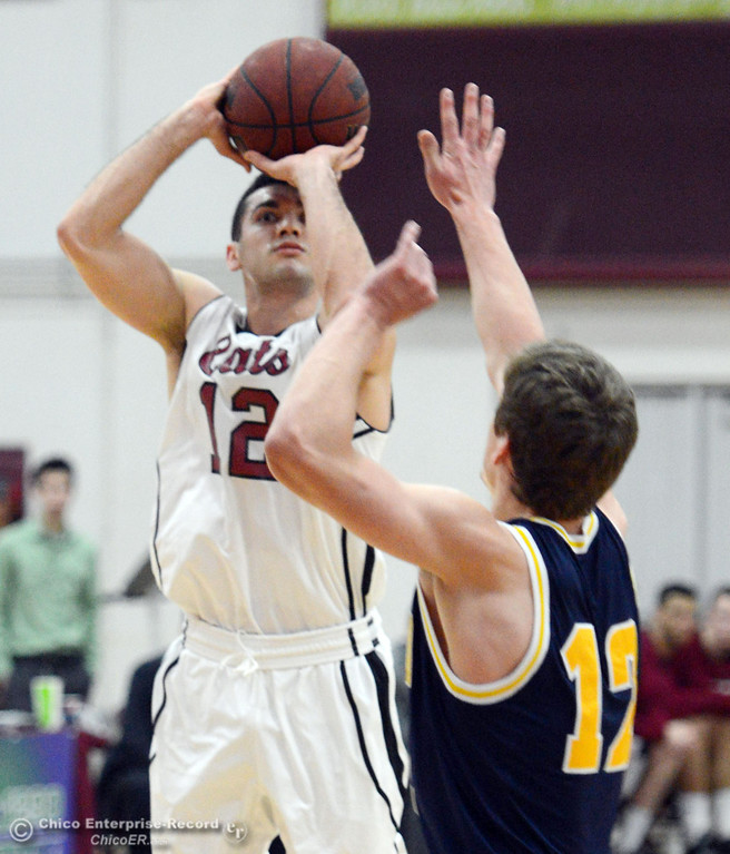 Description of . Chico State's #12 Giordano Estrada (left) takes a shot against UC San Diego's #12 Adam Klie (right) in the first half of their men's basketball game at CSUC Acker Gym Friday, February 7, 2014 in Chico, Calif.  (Jason Halley/Chico Enterprise-Record)