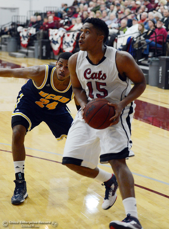 Description of . Chico State's #15 Amir Carraway (right) dribbles against UC San Diego's #24 Treavon Francis (left) in the first half of their men's basketball game at CSUC Acker Gym Friday, February 7, 2014 in Chico, Calif.  (Jason Halley/Chico Enterprise-Record)